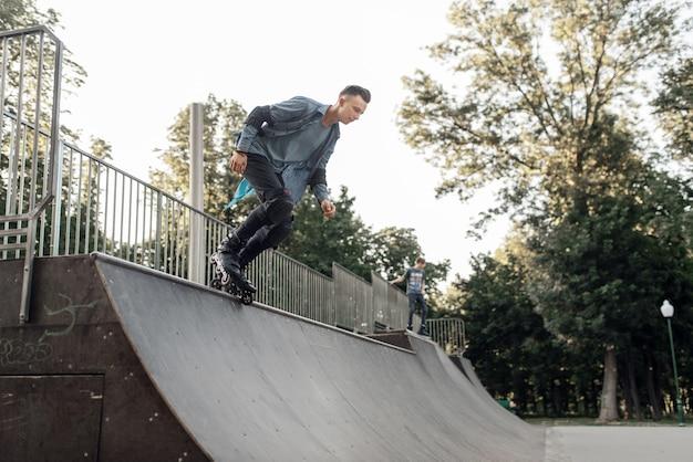 ローラースケート、ランプを降りる若い男性スケーター。アーバンローラースケート、アウトドアでのアクティブエクストリームスポーツ
