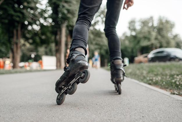 ローラースケート、夏の公園で転がる若いスケーター、足の背面図。