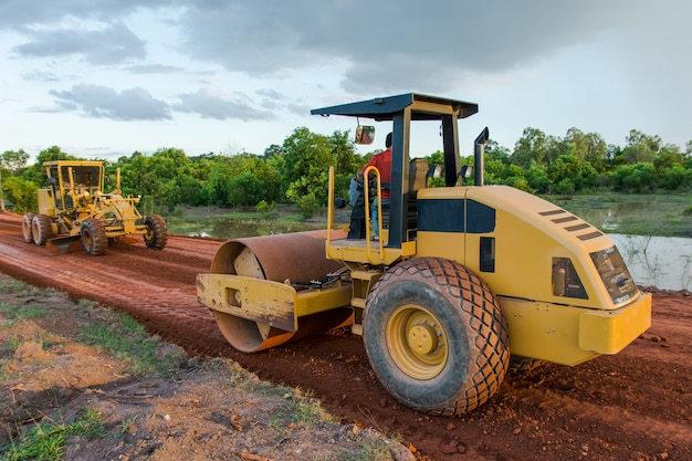 Roller steamroller or vibratory roller machine and motor graderworking on road constructio