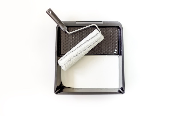 Roller with a paint tray and white paint