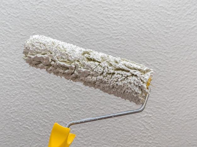 Ролик с белой краской на светлой стене. концепция ремонта.
