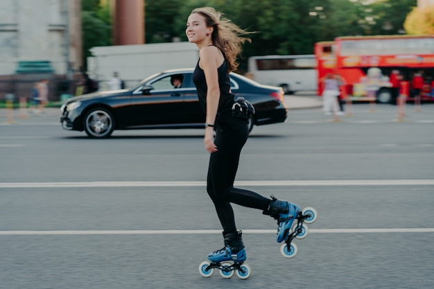 Rollerblading concept. active fit young woman rides on skates along busy road with transport moves actively has hair floating on wind being in good physical shape enjoys rest and recreation.