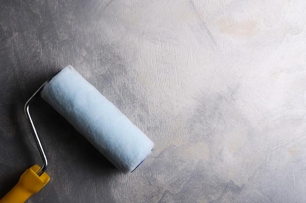 灰色のコンクリートテーブルにペイントするためのローラー。上面図