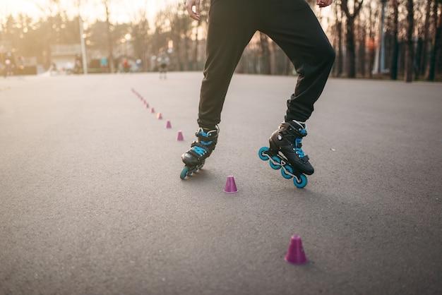 ローラースケート選手、公園でのローラースケートのトリックエクササイズ