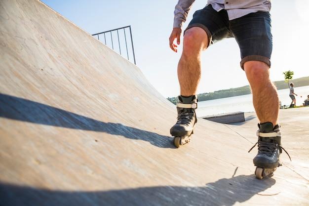 Rollerskater's leg rollerskating in skatepark