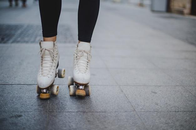 Женщина, носить rollerskates, стоя на тротуаре