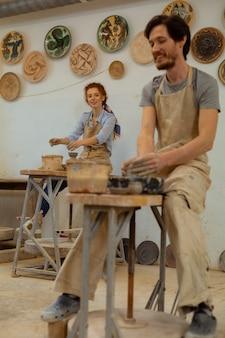 ローリングブラックホイール。家具付きの装飾されたスタジオで彼の生姜の女の子と一緒に働いている黒髪の男の笑顔
