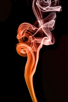 Rolling colorful smoke on black background