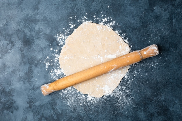 Rolling dough on a table with a wooden rolling pin.