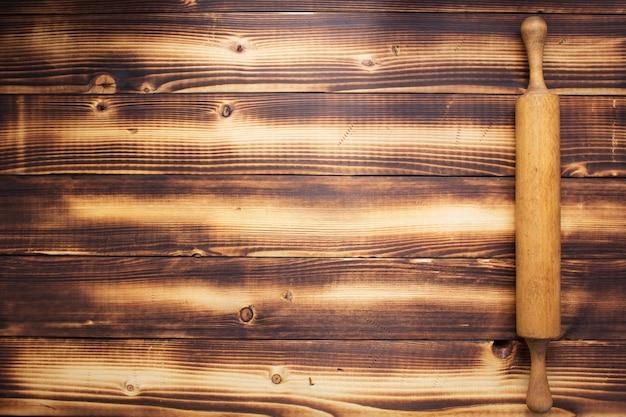 소박한 보드 나무 판자 배경의 롤링 핀, 위쪽