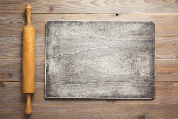 소박한 나무 판자 보드 테이블 배경의 롤링 핀, 위쪽