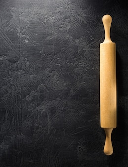 Rolling pin at black background texture