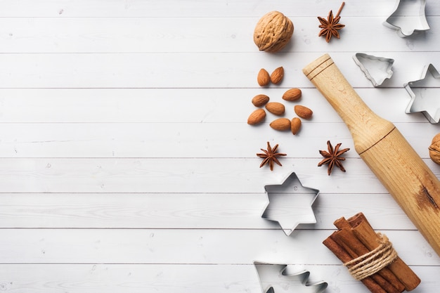 Rolling pin cookie cutters cinnamon cocoa nuts on wood