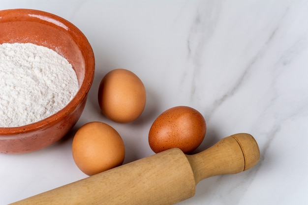 Rolling pin, cup of flour and eggs