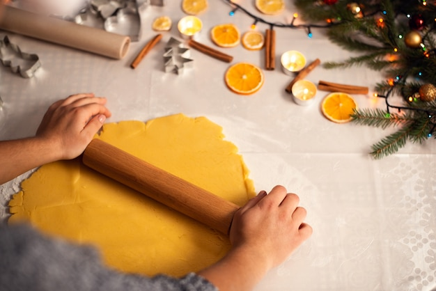 Rolling pin in hands of a young girl rolling dough preparing to cook biscuits for christmas holidays