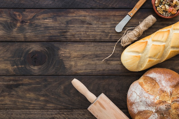 Rolling pin near loaves of bread