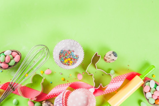 Rolling pin, whisk for whipping, cookie cutters, sugar sprinkling and flour on light green background