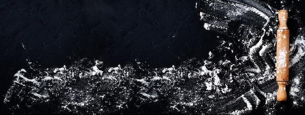 Скалка с мукой на темно-черном фоне выпечки, вид сверху, копия пространства для текста, меню, рецепта. баннер. плоская планировка.