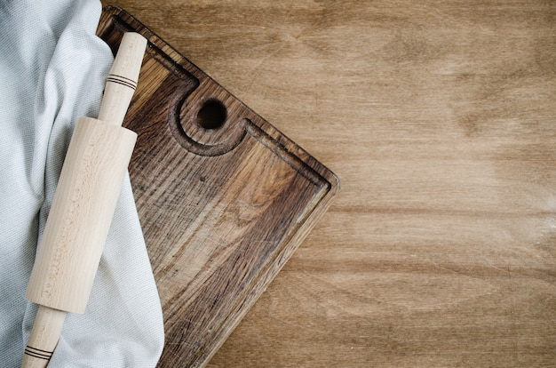 Rolling-pin with kitchen towel on wooden board.