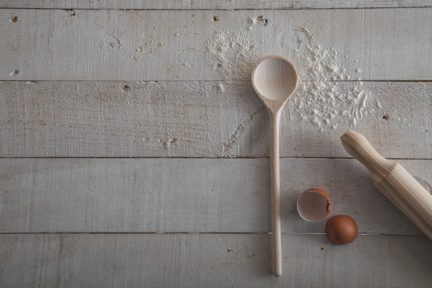 Rolling pin and wooden spoon for making dough, flour and egg on white wooden background.