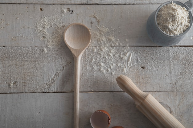 Rolling pin and wooden spoon for making dough on white wooden background.
