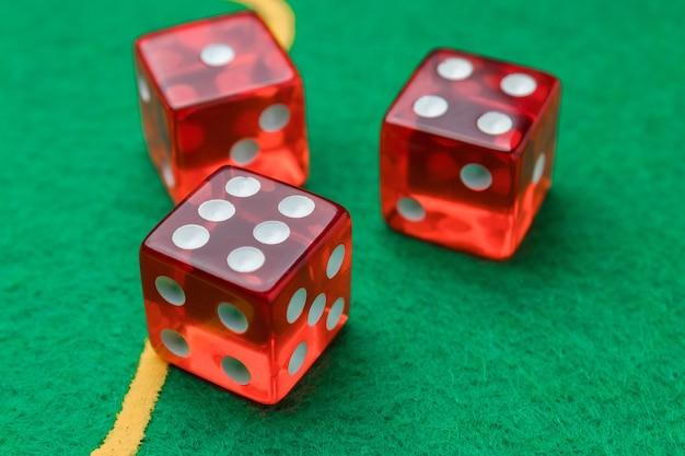 Катящаяся красная игральная кость зеленая поверхность