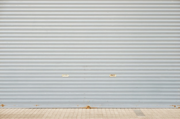 Rolling shutter door of large garage warehouse entrance with concrete tile floor