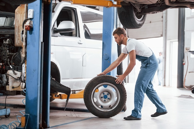 Rolling tire. employee in the blue colored uniform works in the automobile salon.