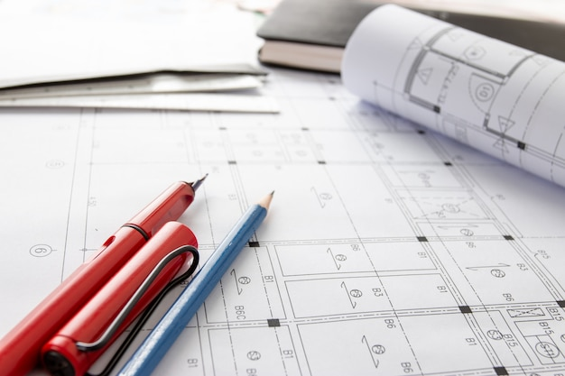 Rolls of architecture blueprints and house plans on the table and architect drawing tools.