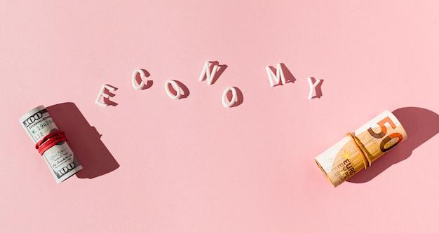 Rotoli di banconote con ombra ed economia parola