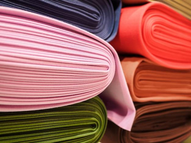 Rolls of bright multicolored fabric close-up.
