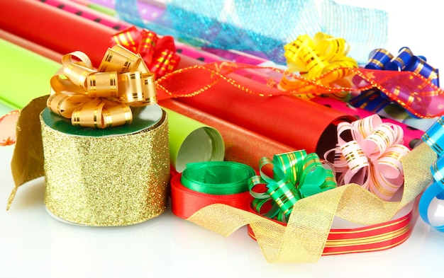 Rolls of christmas wrapping paper with ribbons, bows isolated on white