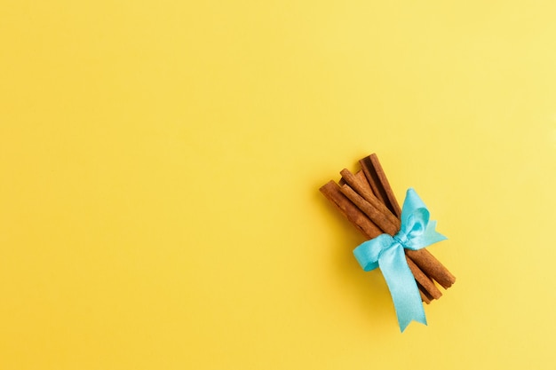 Rolls of cinnamon tied up with ribbon on yellow background