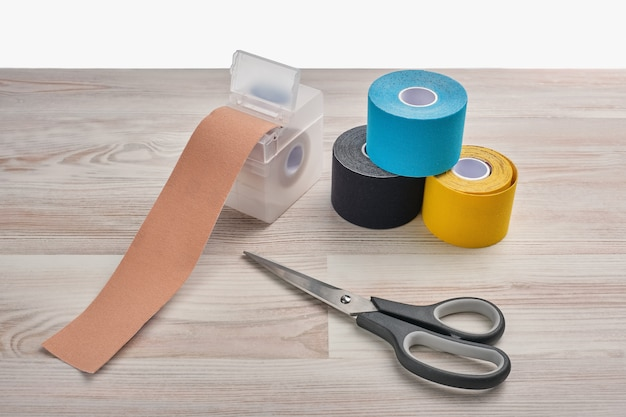 Rolls of colored kinesio tape with a pair of scissors on a wooden background