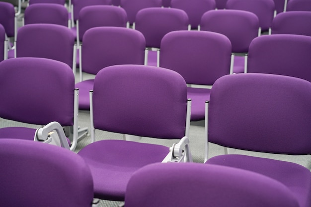 Rolls of empty seats in waiting area for flight departure at the airport. purple seats in airport terminal.