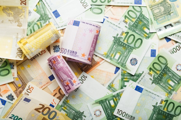 Rolls of euro banknotes on scattered euro money. business, finance, saving, banking concept, exchange rates. frame, copy space, top view.