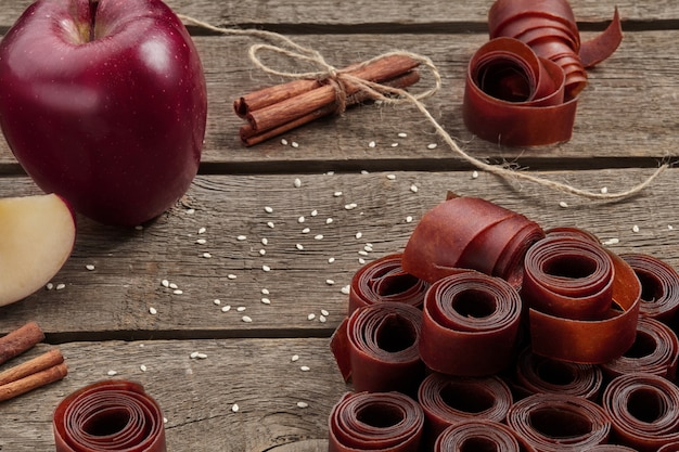 Rolls of fruit leather on wooden surface with apple and cinnamon