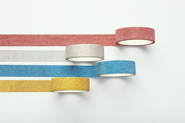 Rolls of glitter tape isolated on white