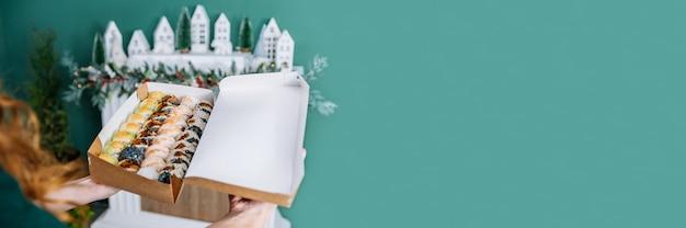 家のインテリアの背景に女の子の手のクラフトボックスで転がります。