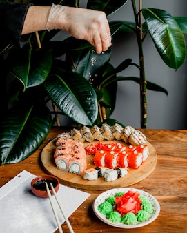 Rolls made from fish on the wooden round surface along with sticks and black sauce on the grey surface