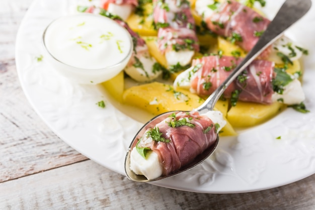 Rolls of mozzarella, basil and parma ham