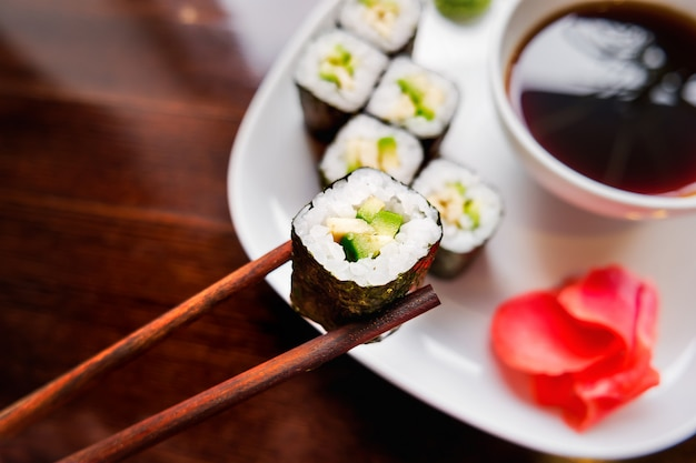 Rolls in nori seaweed with avocado, pickled ginger and soy sauce