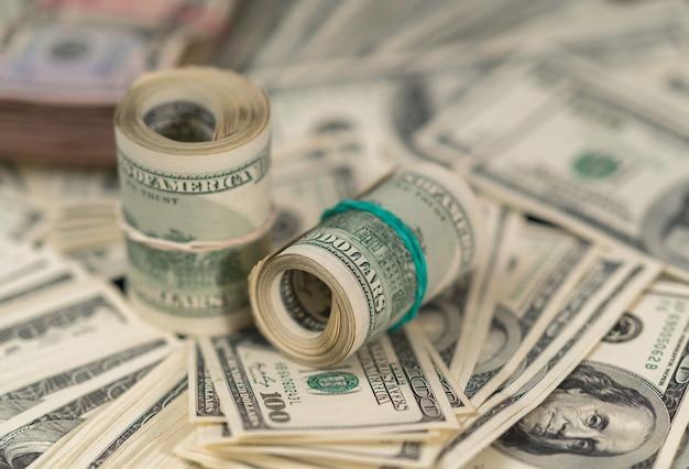 Рулоны 100-долларовых банкнот на кучах денег в концептуальной полной выборочной фокусировке