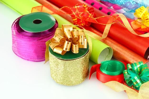 Рулоны рождественской оберточной бумаги с лентами, бантами, изолированными на белом