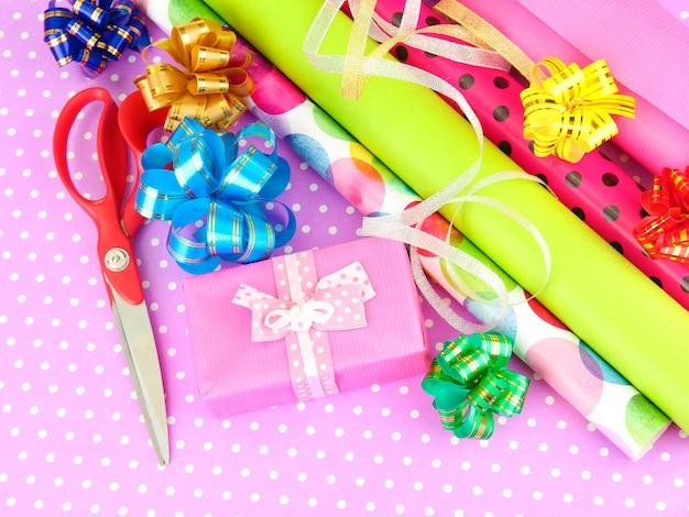 Рулоны рождественской оберточной бумаги с лентами, бантами на цветном фоне