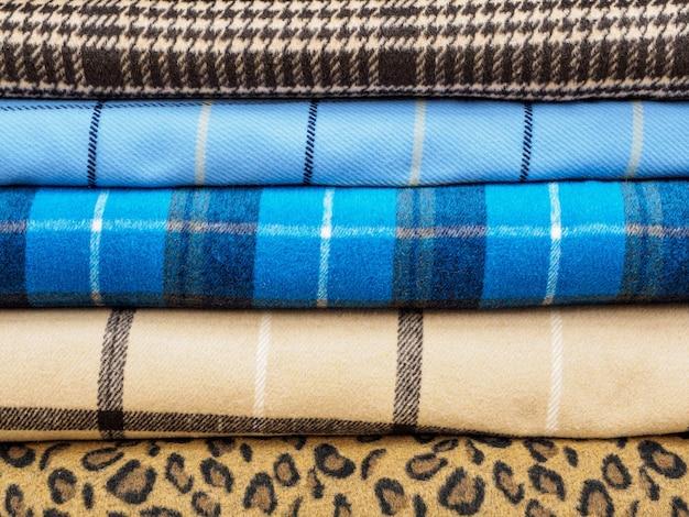 Рулоны из разных клетчатых тканей для пошива пальто крупным планом.