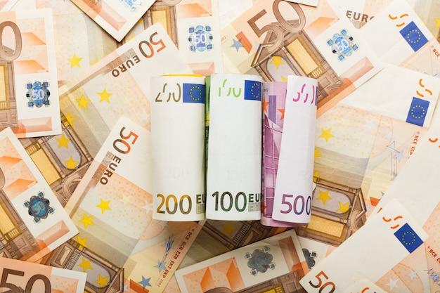 흩어져 있는 유로 돈에 유로 지폐의 롤입니다. 비즈니스, 금융, 저축, 은행 개념, 환율. 프레임, 복사 공간, 평면도.