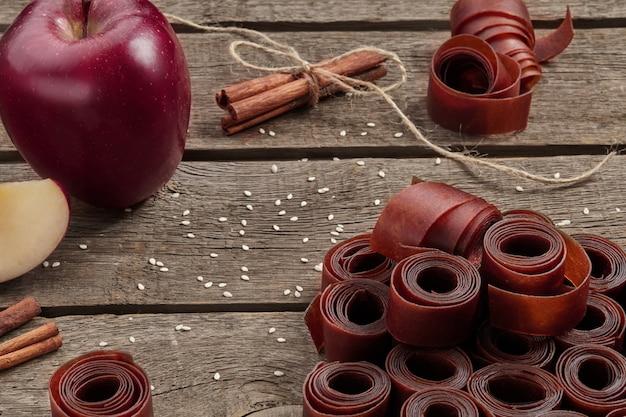リンゴとシナモンと木の表面にフルーツレザーのロール