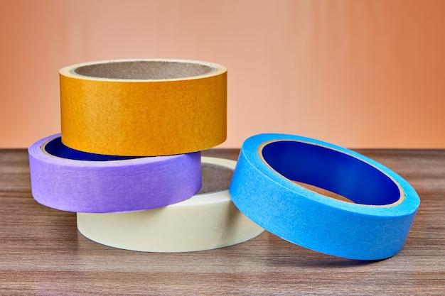 На столе лежат рулоны разноцветной бумаги и пластикового скотча.
