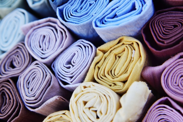 Рулоны разноцветных тканей крупным планом.